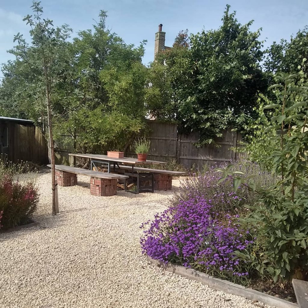 Duck guck goose back garden with white shingle, lavender and scaffold board table and benches