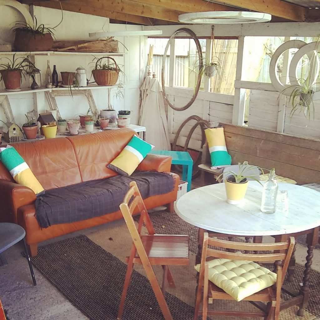 Duck guck goose rear verandah showing sofa with colourful cushions and hanging plants