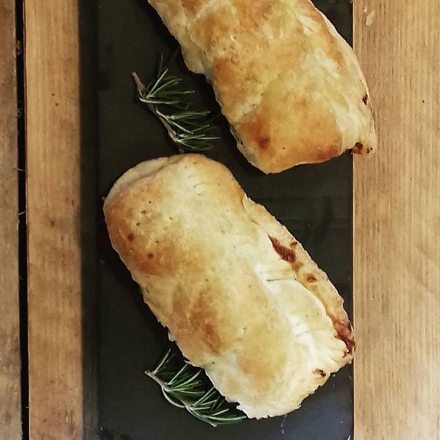 two hot homemade sausage rolls on a slate with sprigs of rosemary